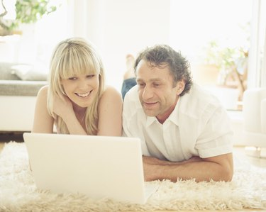 Man and woman using laptop on rug