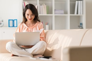 Smiling woman sitting on the couch with laptop