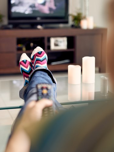 Woman Relax On Sofa Watching Film On TV With Remote