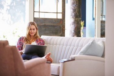 Woman Relaxing On Sofa At Home Using Laptop Computer