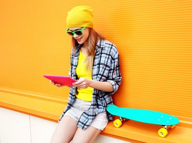 stylish cool girl using digital tablet pc in city