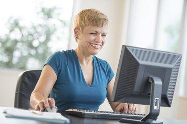 Happy Businesswoman Using Computer At Desk