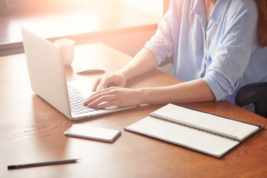 Cropped view of a young businesswoman typing on her laptop