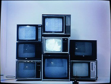 Joystick in front of stack of televisions (video still)