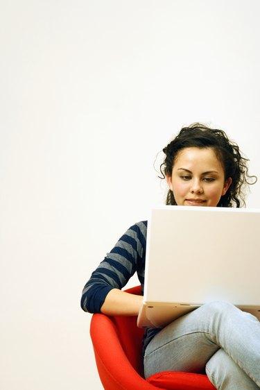 Girl (14-15) using laptop, sitting on chair, smiling