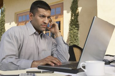 Mid adult man working on laptop at outdoor cafe table