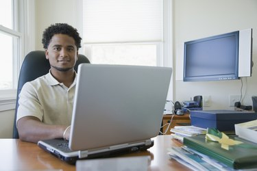 Portrait of a businessman using a laptop in an office