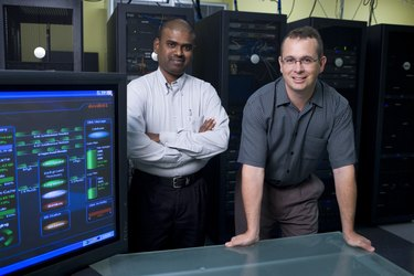 Portrait of two technicians standing in a server room