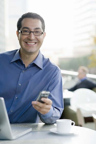 Smiling business man with phone and computer.