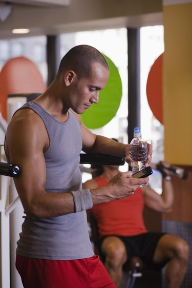 Man with cell phone in gym