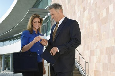 Business man giving card to woman, outdoors