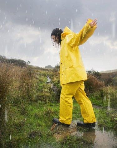 Hispanic woman in rain gear walking in puddle