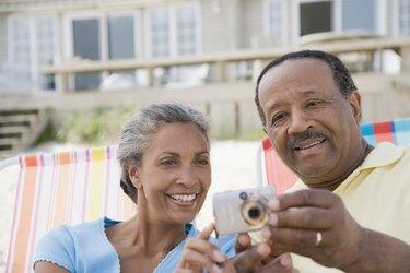 Senior man and a mature woman looking at a digital camera