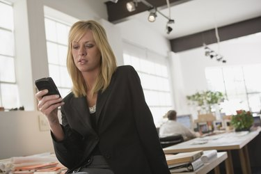 Woman text messaging with cellular phone