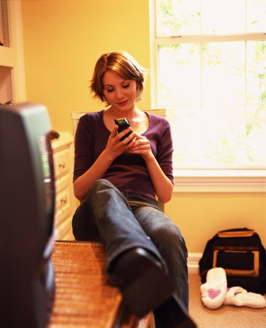 Woman using the phone in a bedroom