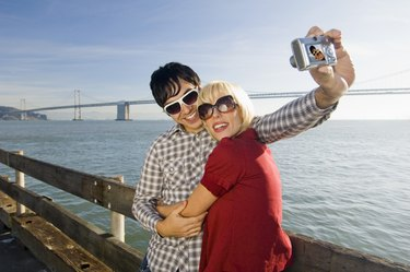 Couple taking picture by water
