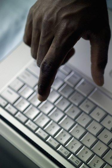 Man's hand above laptop computer, close-up, part of, selective focus