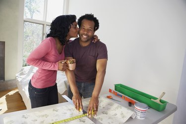 African man measuring wall paper getting kiss from wife