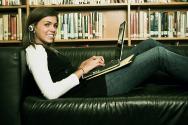 Student sitting on a couch with a laptop and listening to music