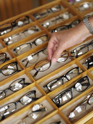 Man selecting a pair of eyeglasses from display case in shop, close-up of hand