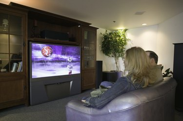 Couple watching widescreen TV set in bookcase