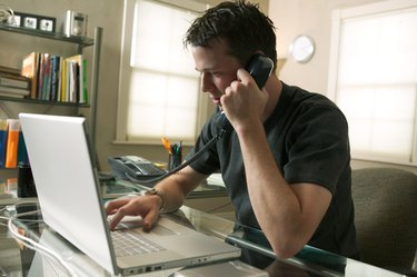 a young caucasian man sits working at his computer and on the phone in his home office