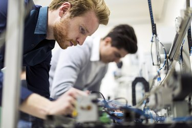 Two young handsome engineers working on electronics components