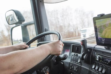 Male arms driving a truck on the road