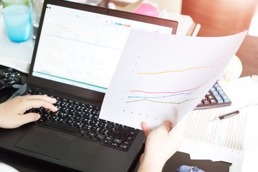 Hands of businesswoman holding analysis chart with laptop and ca