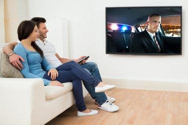 Happy Couple In Livingroom Watching Movie