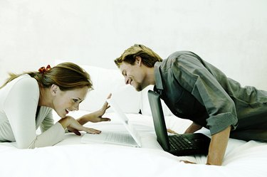 Playful couple with laptops