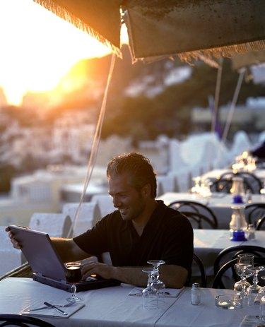 Man using laptop computer at outdoor cafe at sunset