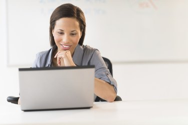Businesswoman With Hand On Chin Using Laptop At Desk