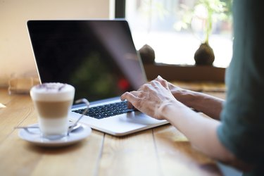 green shirt woman typing blank screen laptop