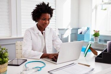 Black female doctor wearing white coat at work in