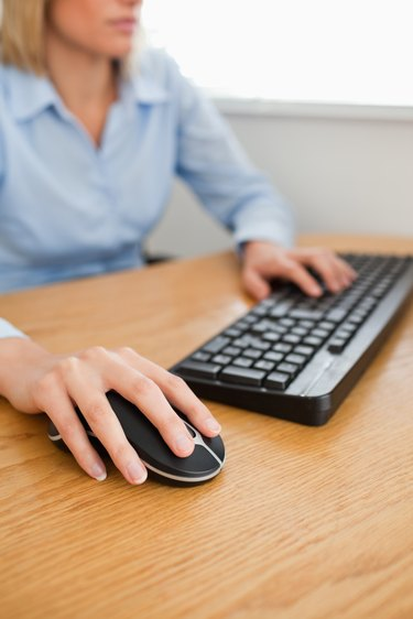 Blonde businesswoman with hands on mouse and keyboard