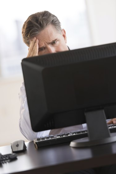 Tensed Businessman Looking At Computer Monitor