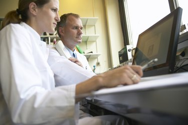 Two doctors looking at computer screen, low angle view
