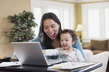 Mixed Race mother and baby looking at laptop