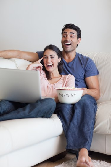 Portrait of a laughing couple watching a movie while eating popcorn