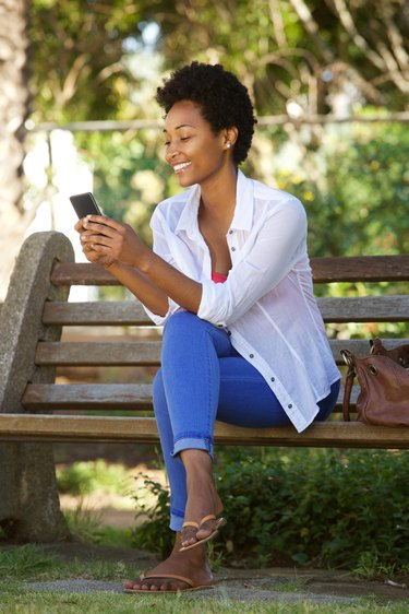 Young lady relaxing a park bench and using mobile phone