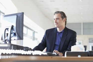 Businessman at desk in office, looking at monitor, low angle view