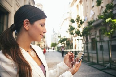 Businesswoman in street using hand held computer, smiling, close-up