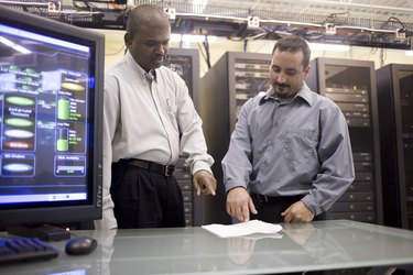 Two technicians standing in front of a network server