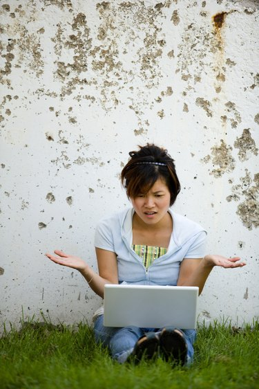 Frustrated woman on laptop computer outdoors