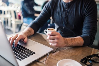 Man holding coffe in one hand and working on laptop