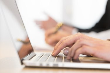 Woman using laptop in office during a meeting. Close-up hands