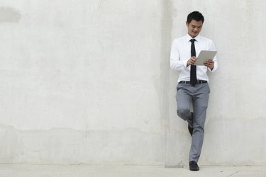Young businessman reading while leaning on a blank wall