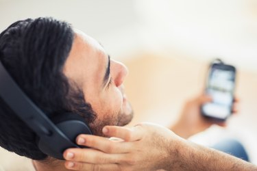 Close up on handsome man listening to music on his smartphone