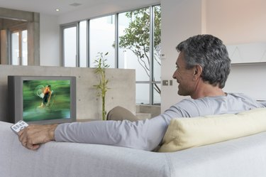 Man relaxing on sofa watching television, rear view